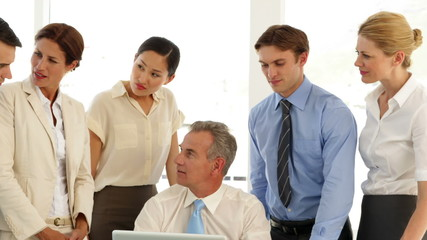 Business team talking in front of laptop