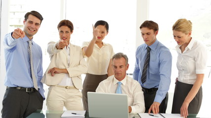 Business team talking in front of laptop then pointing to camera