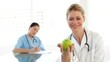 Smiling doctor showing a green apple