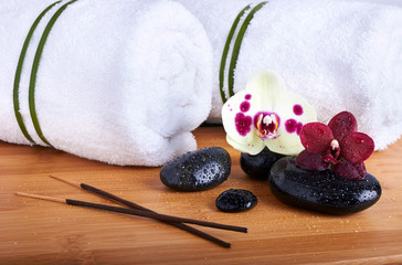 Spa stones and orchids on the wooden background