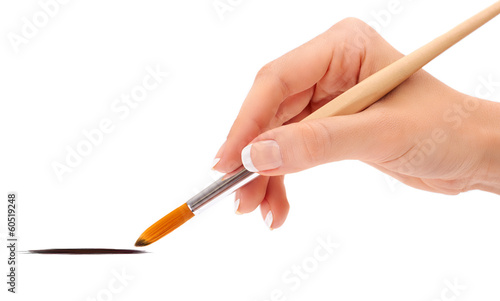Female hand holding paint brush isolated