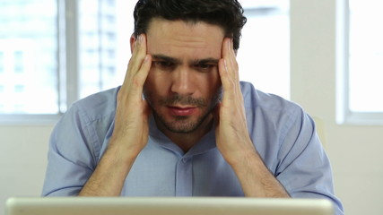 Stressed businessman looking at laptop
