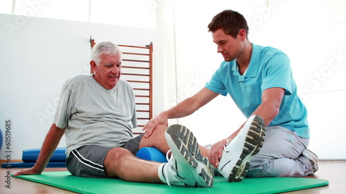 Physiotherapist helping patient with his knee mobility
