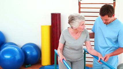 Physical therapist helping patient to walk with parallel bars