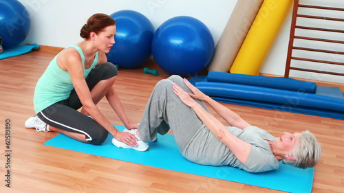 Trainer helping her elderly client do sit ups