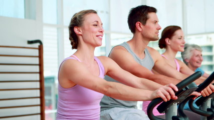 Happy fitness group doing a spinning class