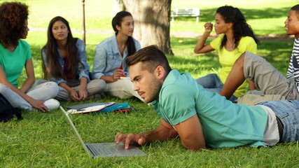 Smiling student using his laptop in front of his friends
