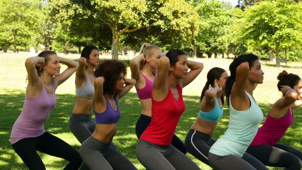 Fitness class doing squat sequence together