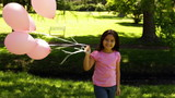 Little girl carrying balloons for breast cancer awareness