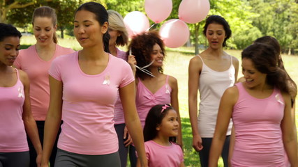 Women going on a walk for breast cancer awareness in the park