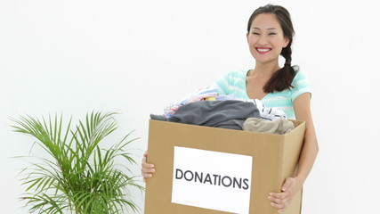 Pretty brunette holding donation box full of clothes