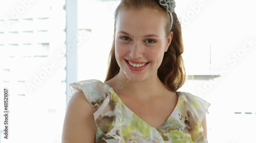 Model in floral dress walking towards camera and smiling
