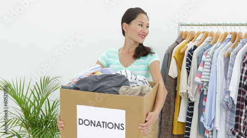 Pretty asian brunette holding donation box full of clothes