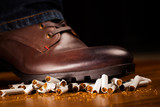 shoes trampling down on cigarettes