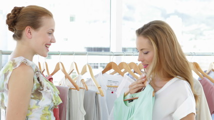 Two pretty friends looking through clothes rails