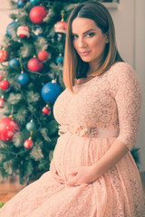 Christmas pregnant woman beside fir tree