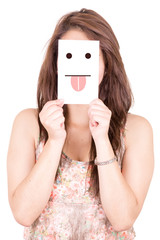 Young woman holding a paper with a cute smiley face with tongue