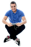 Young guy enjoying music and using tablet pc