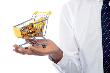 Man holding a shopping cart filled with gold coins