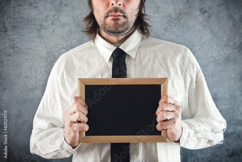 Businessman holding blank blackboard