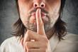 Businessman making hush gesture