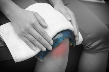 a woman applying cold pack on  swollen hurting knee after accide