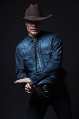 Modern fashion cowboy. Wearing brown hat and blue jeans shirt. P