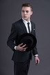 Retro fashion fifties young businessman with hat wearing dark su