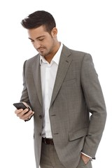 Young businessman texting on mobilephone