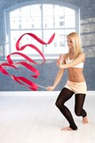 Happy gymnast girl exercising with ribbon