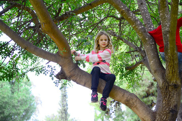 Blond girl climbing on a tall tree