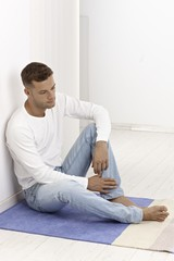 Young man sitting on floor looking sad
