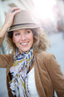 Cheerful blond woman in town with hat on