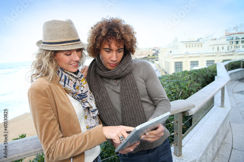 Couple of tourists using digital tablet