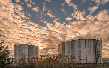 Industrial tanks on dramatic sunset
