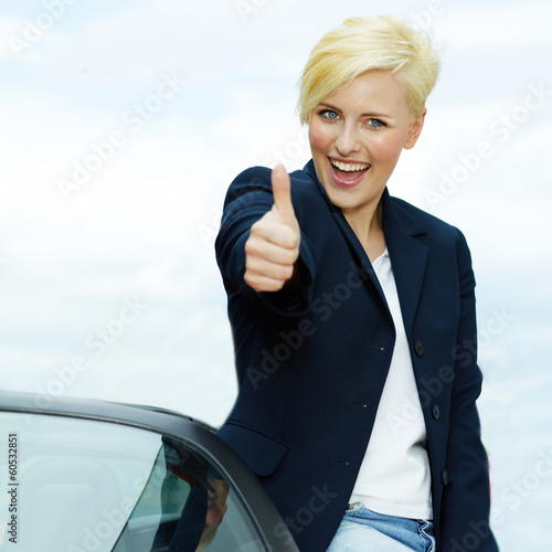 Pretty woman shows thumb up for driving enjoyment