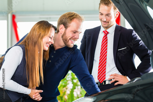 Young Couple and seller with auto in car dealership