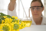 Laboratory worker with beaker of vegetable oil