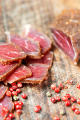 Slices of cured meet and pepper on wooden table