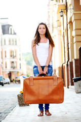 Sad looking girl with luggage in city