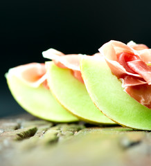Serrano ham with melon on old wooden table three