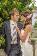 Groom and bride on background of green trees
