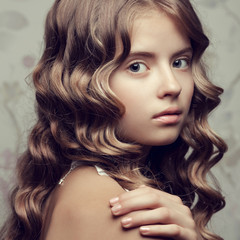 Portrait of a little princess with long curly glossy hair
