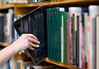 closeup hand putting a tablet pc in the shelves in the library