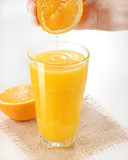Hand squeezing a fresh orange on glass - Orange juice