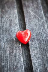Red heart on the shabby wooden board
