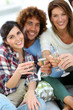 Closeup of friends cheering with glass of wine
