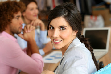 Portrait of smiling business girl attending meeting