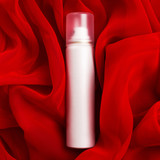 Beauty spray (aerosol) over red vapory and wavy cloth background