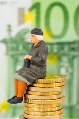 Rentnerin sitzt auf Geldstapel